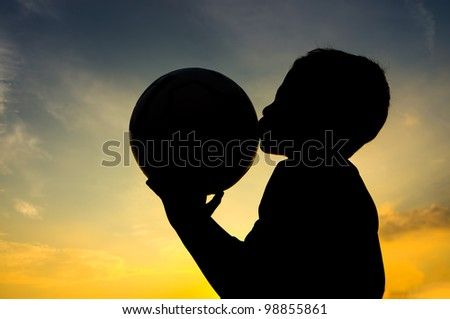 Boy kiss the ball during sunset - stock photo