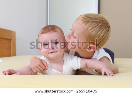 Boy kissing a baby on the cheek lying on a bed - stock photo