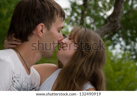 boy kissing a girl in the woods