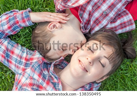 boy kissing his mom on grass - stock photo