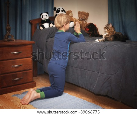 boy kneeling at bedside saying prayers in pajamas - stock photo