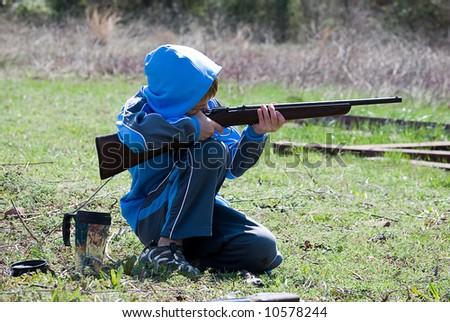 Boy kneeling while shooting rifle - stock photo