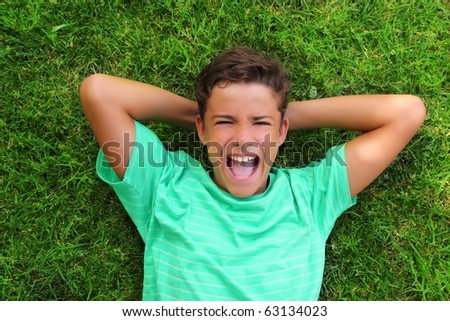 boy laughing happy teenager laying green grass - stock photo