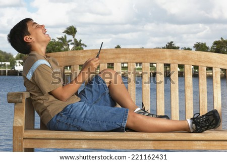 Boy laughing on bench - stock photo