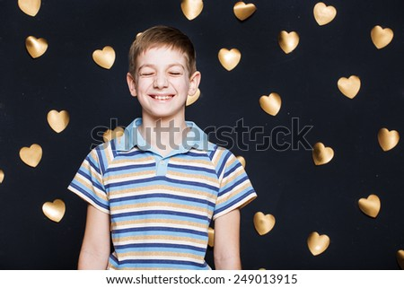 Boy laughing on golden hearts background - stock photo