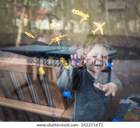 boy laughing through window with stickers of planes and cars - stock photo