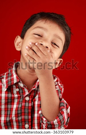Boy laughs with his mouth closed by in a red background - stock photo