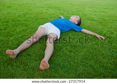 boy lay on the green grass - stock photo