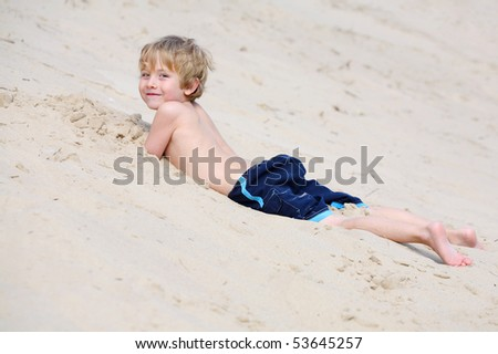 Boy laying in the sand at the bottom of a sand dune - stock photo