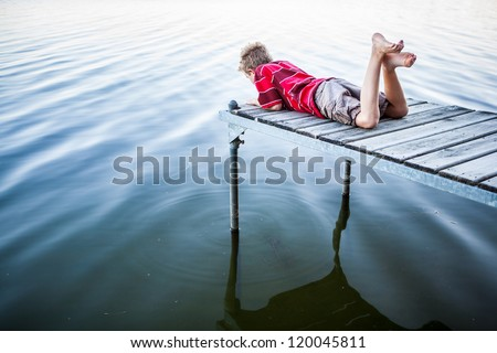 Boy laying on a dock by a lake - stock photo