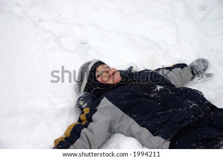 Boy laying on back in snow (5yr old) - stock photo