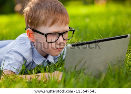 boy laying on green grass in the park with laptop - stock photo