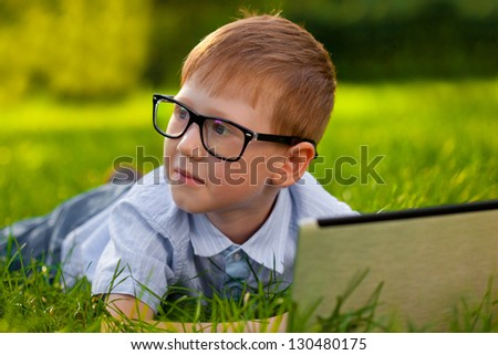 boy laying on green grass in the park with laptop, looking to the right side - stock photo