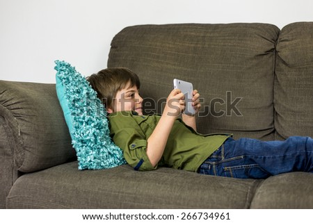 boy laying relaxed on sofa playing on his tablet - stock photo