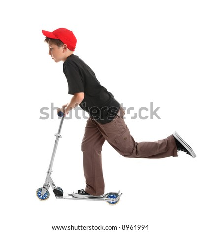 Boy  leaning forward and pushing the scooter with one foot to pick up speed - on a white background. - stock photo