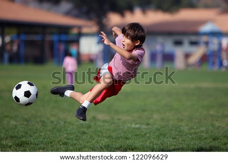 Boy leaps up playing soccer in the park - authentic action - horizontal with copy space - stock photo