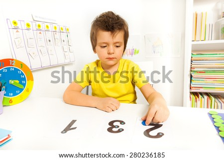 Boy learn to count put coins on the numbers  - stock photo
