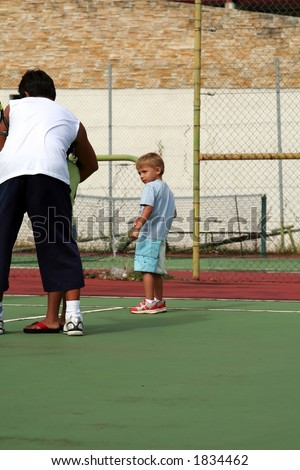 boy learning tennis on a court