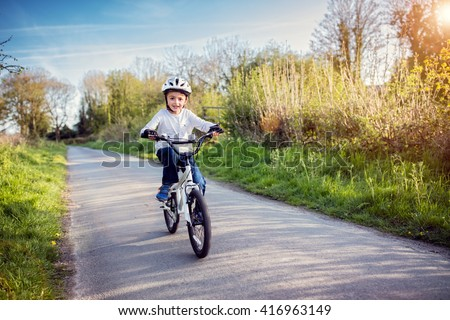 Boy learning to ride his bike on a country track road concept for safety and child development - stock photo