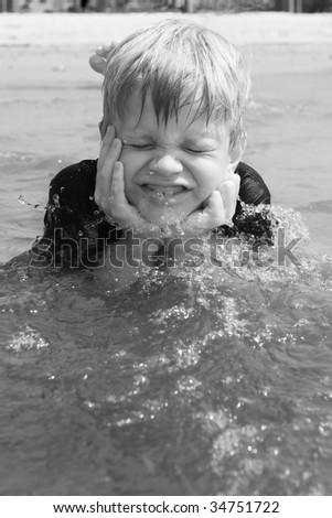 Boy letting wave splash on face - stock photo