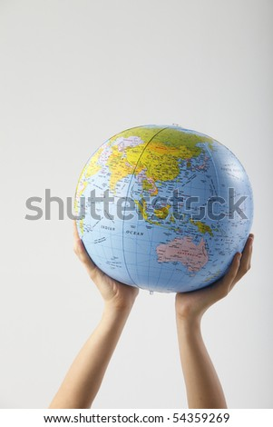 boy lifting a globe with two hands