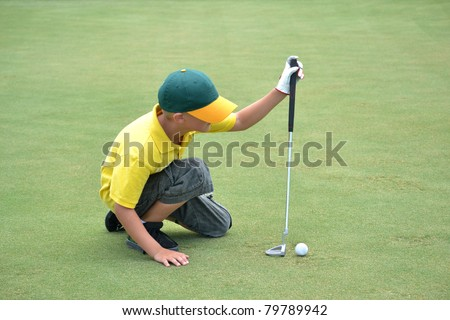 boy lining up a putt on the green - stock photo