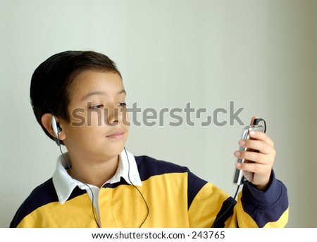 Boy listening music in an MP3 player. Tight focus on boy's face. - stock photo