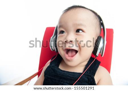 boy listening to music on headphones against white - stock photo