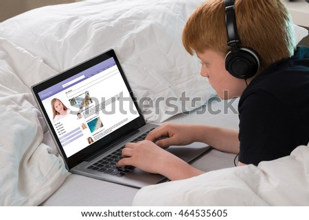 Boy Listening To Music While Chatting On Social Networking Site Using Laptop