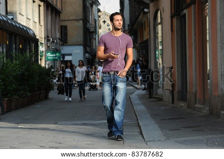 boy listening to music with mp3 walking around the city - stock photo