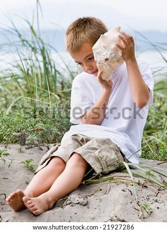 Boy listening to seashell at beach - stock photo