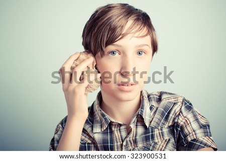boy listening to the sound of the sea inside a seashell - stock photo