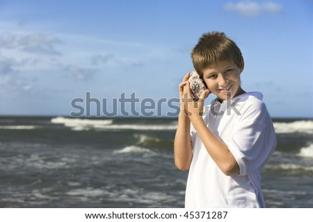 Boy listens to a shell at the beach. Horizontal shot. - stock photo