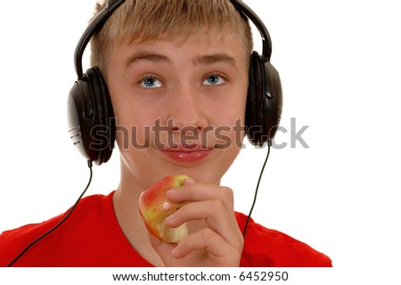 boy listens to music in headphones and eats an apple.