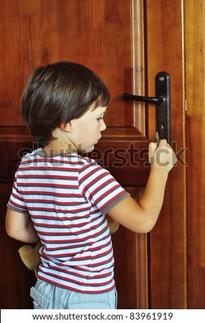 Boy locking the door - stock photo