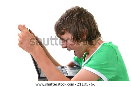 Boy looking angry whilst holding computer - stock photo