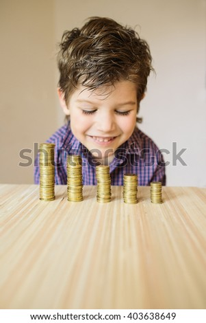 Boy looking at coins on a table - stock photo