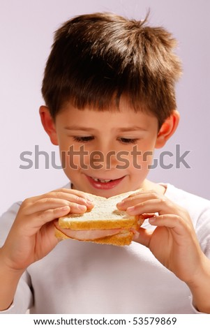 boy looking at his sandwich, selective focus on hands and sandwich - stock photo