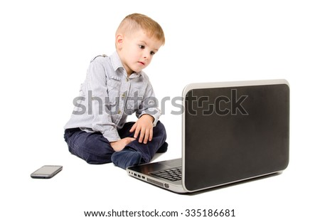 Boy looking at laptop screen sitting isolated on a white background - stock photo