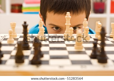 Boy looking at piece of chess - stock photo