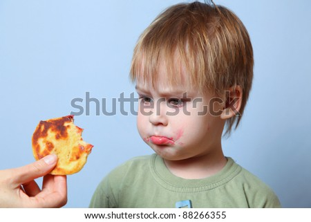 boy looking at small cake - stock photo