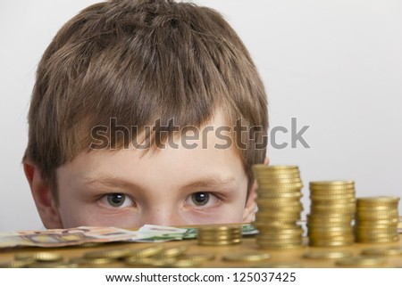 Boy looking at towers of money - stock photo