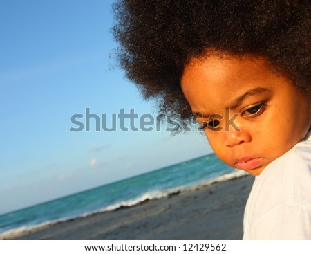 Boy looking down at the sand - stock photo
