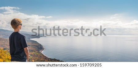 Boy looking down from the top  (Cape Breton, Nova Scotia, Canada) - stock photo