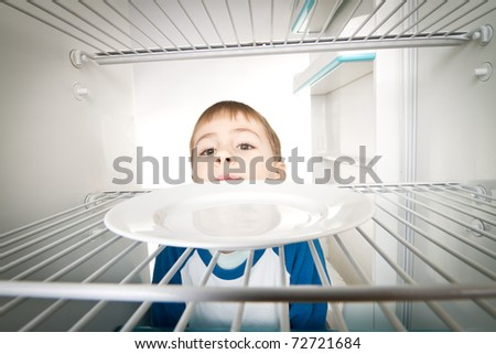 Boy looking into empty refrigerator.