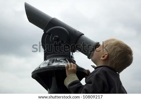 Boy looking into the sky through a telescope. - stock photo