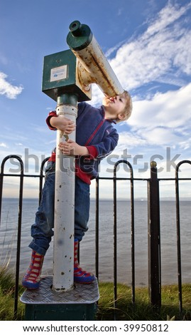 Boy looking into the sky through wrong end of a telescope. - stock photo