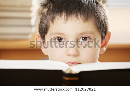 Boy looking over open book with black cover closeup photo
