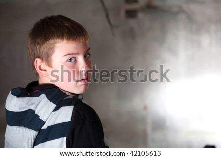 Boy looking over the shoulder against grunge background with copy space, neutral emotion check more of the same model - stock photo