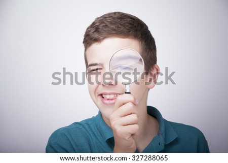 Boy looking through a magnifying glass against grey background